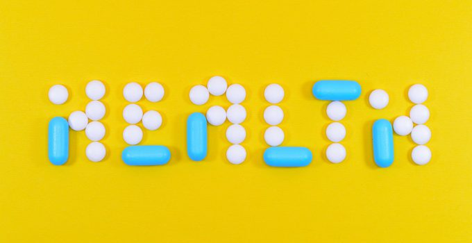 white and blue medical pills spelling the word 'health' in a yellow background